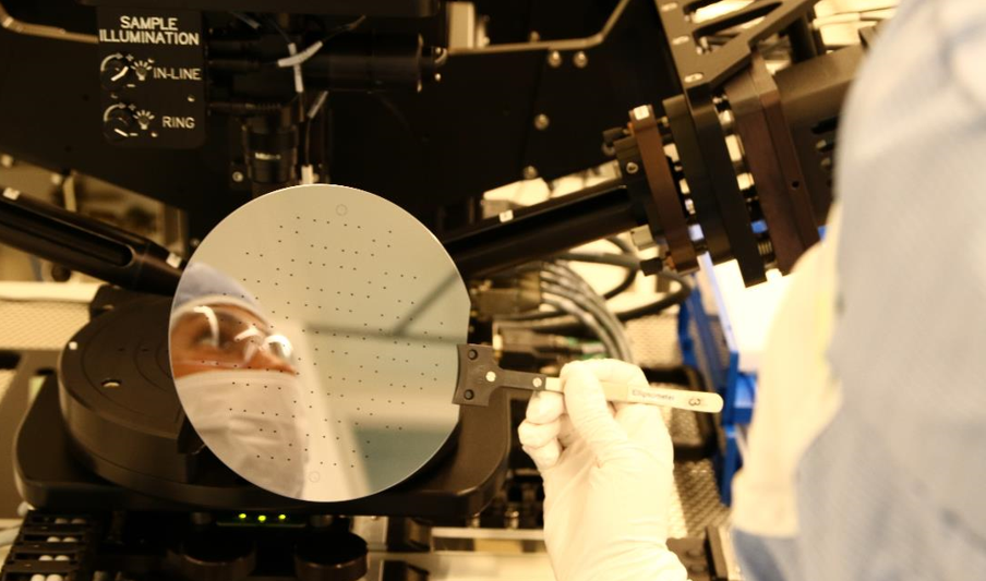Researcher and blog author Elizaveta Vereshchagina in the laboratory. Microfluidics technology has a variety of applications, including DNA analysis and organ-on-a-chip. The photo shows a 6-inch silicon wafer during processing in cleanroom. The dots are inlets to and outlets from the microfluidic channel.
